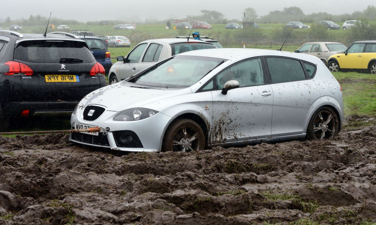 Эвакуатор вытягивает машину из грязи